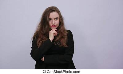 Young Attractive Woman Brunette In In A Black T-Shirt, Sweater On White Background, Terrified Female Hands Are Clenched Into Fists And Held To Her Mouth. The Concept Of Fear, Human Experiences