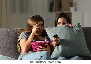 Terrified friends watching tv in the night at home