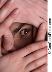 Terrified look. Close-up of human eye looking through the human hands covering face