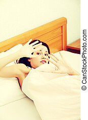 Terrified woman defensing with her hands in bed.