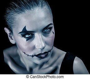 Closeup portrait of terrifying witch with creepy makeup and aggressive look, isolated on black background, Halloween party concept