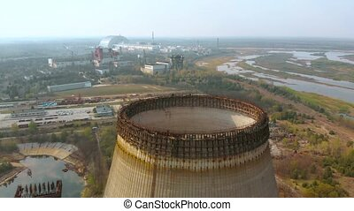 Chernobyl nuclear power plant. Cooling tower overlooking the nuclear power plant in Chernobyl. View of the destroyed nuclear power plant. Territory near Chernobyl NPP, aerial view, sideways movement.