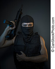 Terrorist, a man dressed in a bulletproof vest and balaclava, is armed with pistols and machine guns