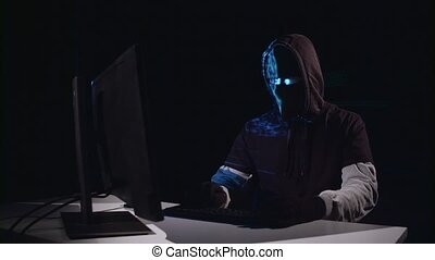 Terrorist hacking computer sitting in a dark room. Black...