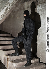 Terrorist in black mask on staircase