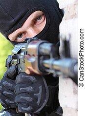 Terrorist in black mask with gun
