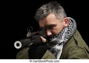 Terrorist in shemagh whit gun, isolated in black background