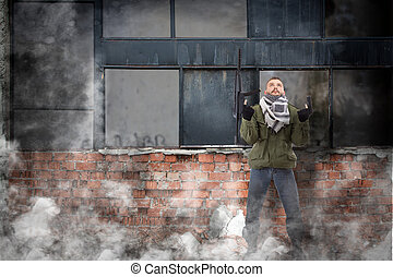 Terrorist with rifle, grunge buildings in background