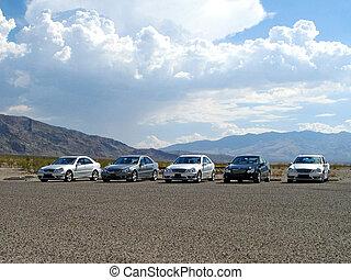five gorgeous, luxury sports cars aligned door-to-door in the hot desert