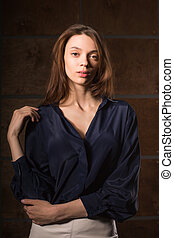 Test shooting for young stylish girl wearing blue silk blouse, posing in the shadows