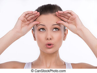 testa, wrinkles., surpreendido, mulher jovem, tocar, dela, testa, e, olhar, enquanto, isolado, branco