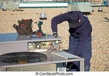 Testing roof top unit - Worker testing a roof top air...