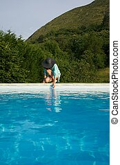 testing water on swimming pool border