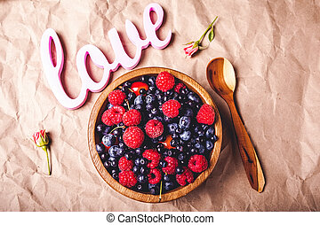Testy fresh berries in wooden plate and spoon