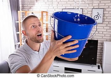 teto, gotas, balde, água, enquanto, segurando, vazamento, homem