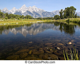 Cathedral Group of Teton Range rises and reflects in Sanke River at Schwabacher's Landing with visible underwater stones.