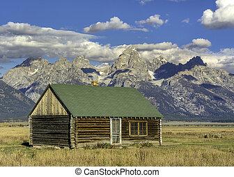 Tetons backdrop and rustic log cabin