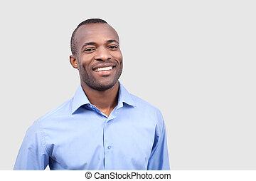 tevreden, man., vrolijk, jonge, zwarte man, het glimlachen, aan fototoestel, terwijl, staand, vrijstaand, op, grijze , achtergrond
