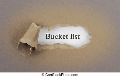 Text appearing behind torn brown envelop - Bucket list