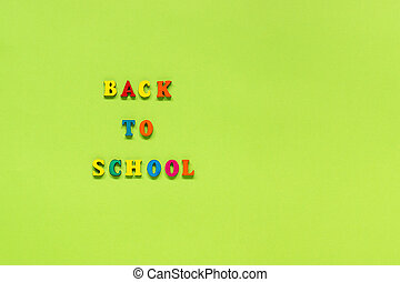 Text Back to school from multi colored letters on green paper background Concept Education Top view Copy space Template for your design