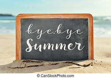 text bye, bye summer in a chalkboard on the beach