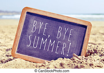 text bye, bye summer in a chalkboard on the beach - closeup...