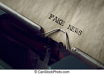 text fake news written with a typewriter - closeup of an old...