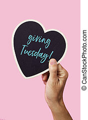 text giving tuesday in a heart-shaped sign - the hand of a ...