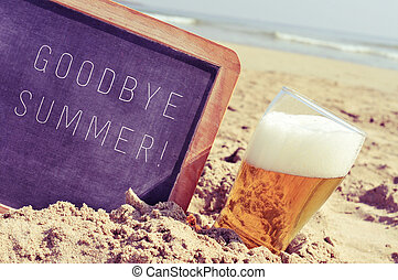 text goodbye summer in a chalkboard and a glass of beer on the beach