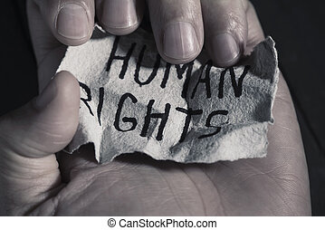 text human rights in a piece of paper - closeup of the hand...