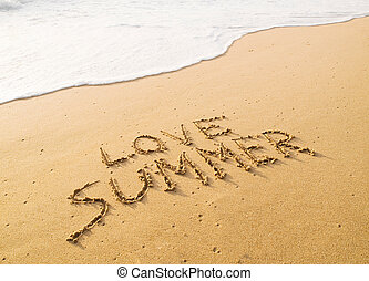 """Text """"love summer"""" written in the sand on the beach"""