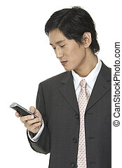 Text Message - an asian businessman sends a text message on...