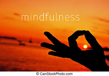 text mindfulness and hand in gyan mudra at sunset - the text...