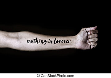 text nothing is forever in a forearm - closeup of a young...