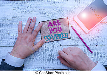 Text sign showing Are You Covered. Conceptual photo Asking about how medications are covered by your plan Hand hold note paper near writing equipment and modern smartphone device.