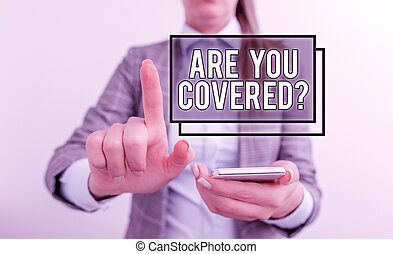Text sign showing Are You Covered Question. Conceptual photo asking showing if they had insurance in work or life Business concept with mobile phone and business woman.
