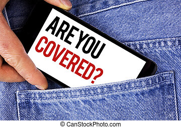 Text sign showing Are You Covered Question. Conceptual photo Health insurance coverage disaster recovery written on Mobile phone holding by man on the Blue Jeans background.