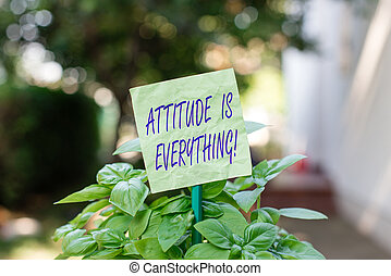 Text sign showing Attitude Is Everything. Conceptual photo Personal Outlook Perspective Orientation Behavior Plain empty paper attached to a stick and placed in the green leafy plants.
