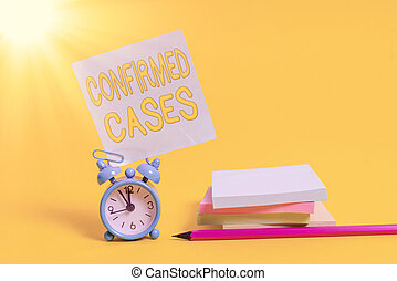 Text sign showing Confirmed Cases. Conceptual photo set of circumstances or conditions requiring action Alarm clock blank pencil sticky note stacked notepads colored background.