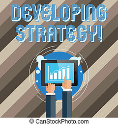 Text sign showing Developing Strategy. Conceptual photo Game plan that sets specific goals and objectives Businessman Hand Touching Pointing to Bar Line Chart on Smartphone Screen.