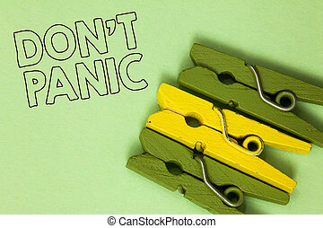Text sign showing Don t not Panic. Conceptual photo sudden strong feeling of fear prevents reasonable thought Three green yellow vintage clothespins clear background Holding things.