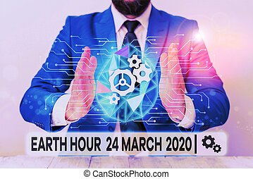 Text sign showing Earth Hour 24 March 2020. Conceptual photo Celebrate Sustainability Save the Planet Lights Off Male human wear formal work suit presenting presentation using smart device.