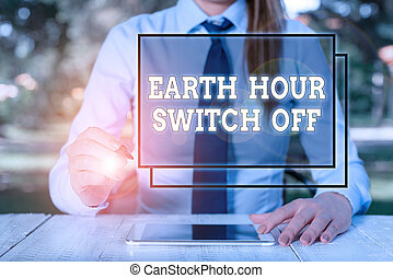 Text sign showing Earth Hour Switch Off. Conceptual photo The Lights Out Event Annual Movement Planet Day Female business person sitting by table and holding mobile phone.