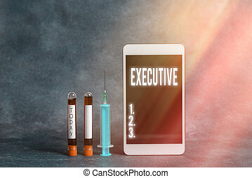 Text sign showing Executive. Conceptual photo belonging to the branch of government that is charged with powers Extracted blood sample vial with medical accessories ready for examination.