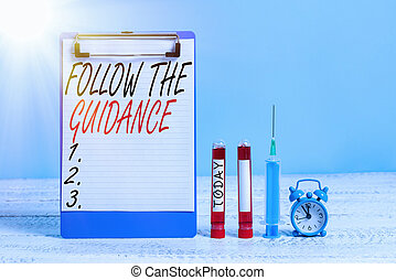 Text sign showing Follow The Guidance. Conceptual photo controlling a course of projectile by builtin mechanism Extracted blood sample vial with medical accessories ready for examination.