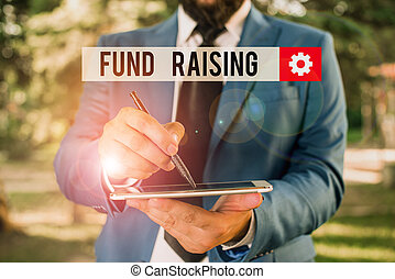 Text sign showing Fund Raising. Conceptual photo the act of seeking to generate financial support for a charity Businessman in blue suite stands with mobile phone in hands.