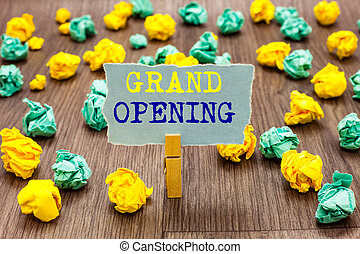 Text sign showing Grand Opening. Conceptual photo Ribbon Cutting New Business First Official Day Launching Clothespin holding gray note paper crumpled papers several tries mistakes.