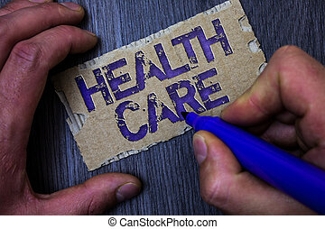 Text sign showing Health Care. Conceptual photo Medical Maintenance Improvement of Physical Mental conditions Man working holding blue marker ideas message paperboard wooden background.