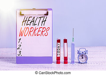 Text sign showing Health Workers. Conceptual photo showing whose job to protect the health of their communities Extracted blood sample vial with medical accessories ready for examination.