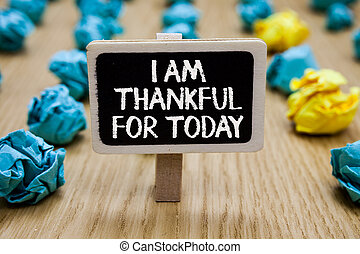 Text sign showing I Am Thankful For Today. Conceptual photo Grateful about living one more day Philosophy Paperclip hold written chalkboard behind paper lumps on woody deck.